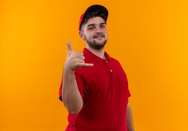Junger lieferbote in roter uniform und mütze, die mich geste mit lächeln auf gesicht nennen