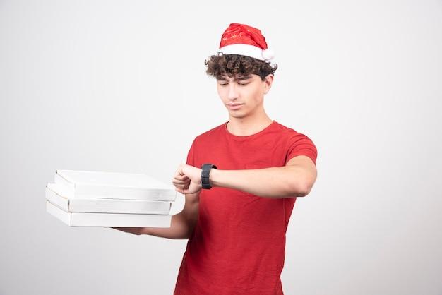 Junger lieferbote mit pizzakartons, die die zeit überprüfen.