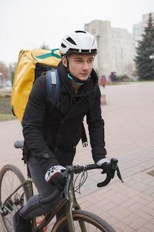 Junger lieferbote mit thermorucksack, der fahrrad reitet