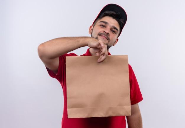 Junger lieferjunge in der roten uniform und in der kappe, die papierpaket hält, das freundlich lächelt