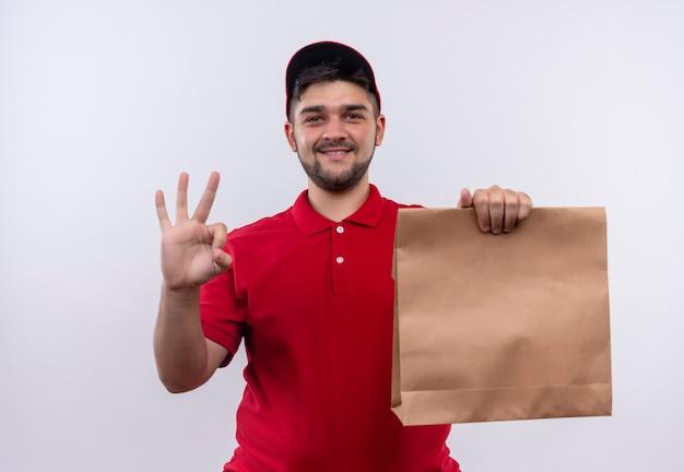 Junger lieferjunge in der roten uniform und in der kappe, die papierpaket hält, das freundliches zeichen ok zeigt