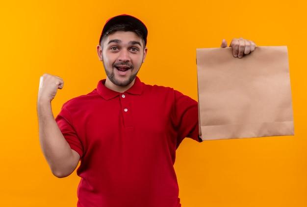 Junger lieferjunge in der roten uniform und in der kappe, die papierpaket hält, das fröhlich die faust hebt, glücklich und aufgeregt