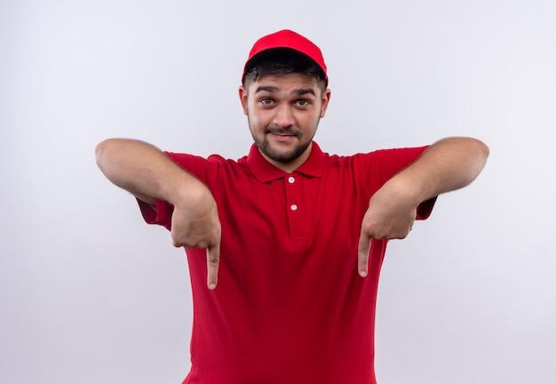 Junger lieferjunge in der roten uniform und in der kappe, die zuversichtlich lächelnd mit den fingern nach unten zeigen