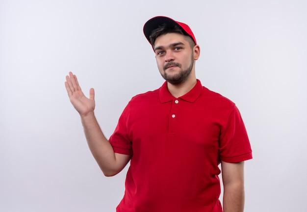 Junger lieferjunge in der roten uniform und in der mütze, die kopienraum mit arm seiner hand darstellt, die zuversichtlich schaut