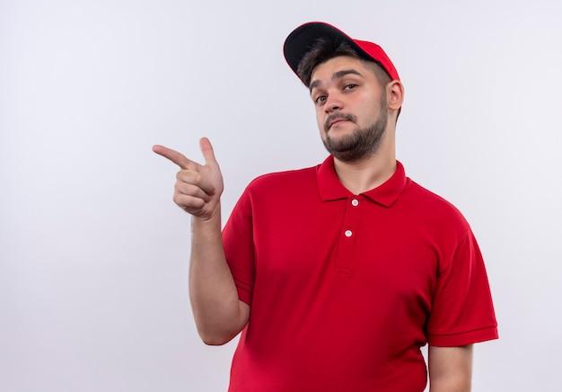 Junger lieferjunge in roter uniform und kappe, die mit dem finger zur seite zeigt, die zuversichtlich schaut
