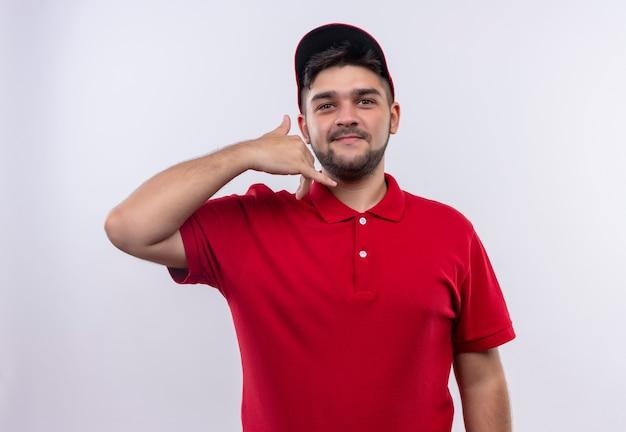 Junger lieferjunge in roter uniform und lächelnd zuversichtlich machen, rufen sie mich geste