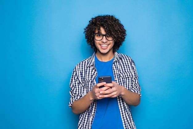 Junger lockiger hübscher mann, der am telefon über lokalisiert auf blauer wand tippt