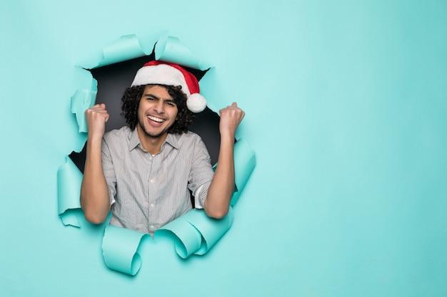 Junger lockiger hübscher mann tragen in weihnachtsmütze mit gewinngeste vom loch auf grünem papier