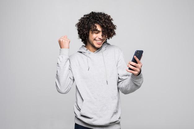 Junger lockiger mann, der mit dem telefon spielt, sieht glücklich und gefistet, nachdem er gewonnen hat, isoliert auf einer weißen wand.