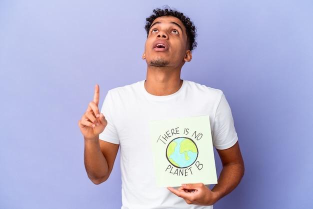 Junger lockiger mann isoliert hält ein theres ist kein planet b plakat, das mit geöffnetem mund nach oben zeigt