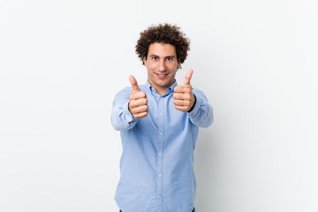 Junger lockiger reifer mann, der ein elegantes hemd mit daumen hoch trägt, jubelt über etwas, unterstützungs- und respektkonzept.