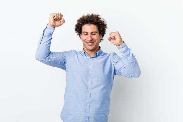 Junger lockiger reifer mann, der ein elegantes hemd trägt, das einen besonderen tag feiert, springt und arme mit energie hebt.