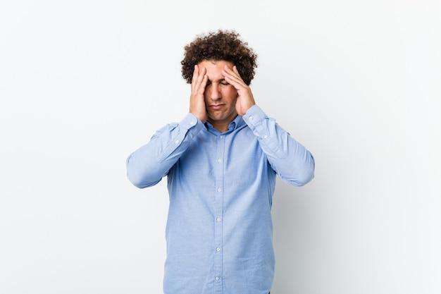 Junger lockiger reifer mann, der ein elegantes hemd trägt, das schläfen berührt und kopfschmerzen hat.