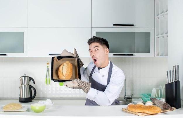 Junger lustiger emotionaler glücklicher männlicher koch in uniform, der hinter tisch steht