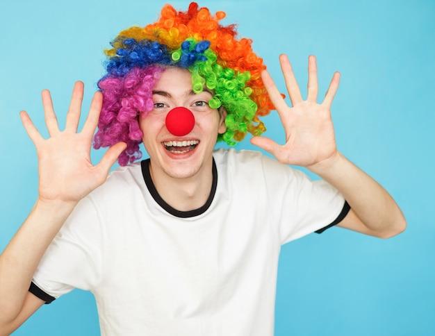 Junger lustiger männlicher jugendlicher im weißen t-shirt in der clownperücke