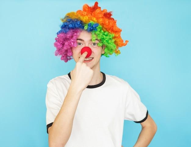Junger lustiger männlicher teenager im weißen t-shirt auf blauem hintergrund Premium Fotos