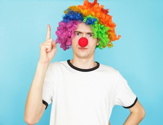 Junger lustiger männlicher teenager im weißen t-shirt auf blauem hintergrund