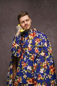 Junger lustiger mann in der blumenkleidung unter verwendung einer banane als telefon