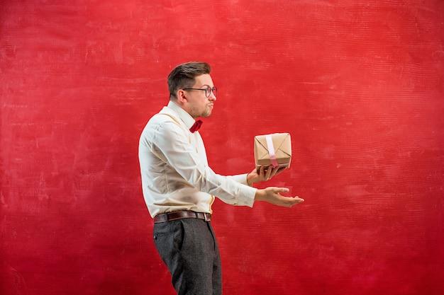 Junger lustiger mann mit geschenk auf rotem studiohintergrund