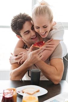 Junger lustiger mann ziehen seine dame mit brot und stau ein, während sie frühstücken