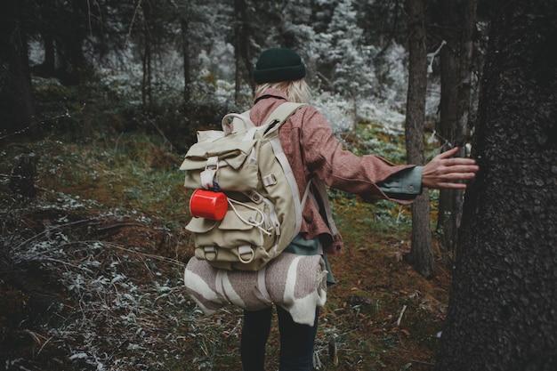 Junger mädchenreisender mit rucksack und ausrüstung im reliktwald
