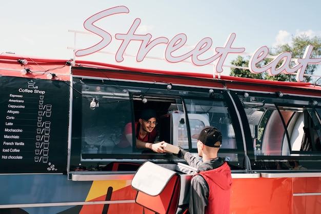 Junger männlicher angestellter eines streetfood-trucks, der eine verpackte kiste mit snacks an den kurier vorbeiführt?