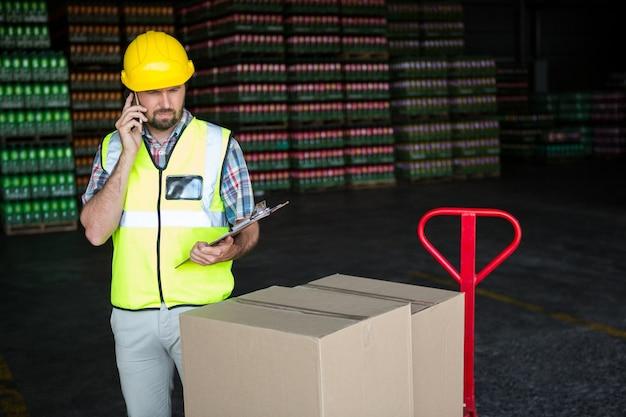 Junger männlicher arbeiter, der am telefon in der fabrik spricht