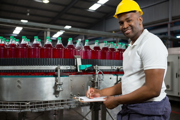 Junger männlicher arbeiter, der in der fabrik bemerkt