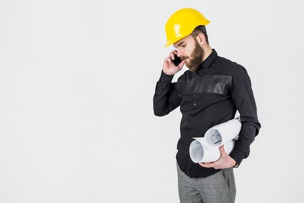 Junger männlicher architekt, der die blaupausen sprechen am handy hält