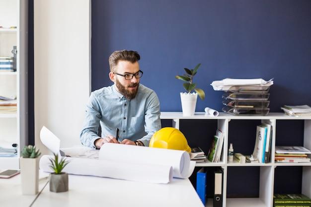 Junger männlicher architekt mit plan auf tabelle am arbeitsplatz