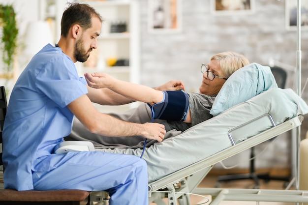 Junger männlicher arzt, der den blutdruck einer älteren frau im pflegeheim misst