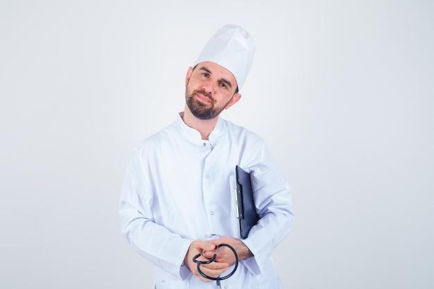 Junger männlicher arzt, der klemmbrett, stethoskop in der weißen uniform hält und sanft schaut. vorderansicht.