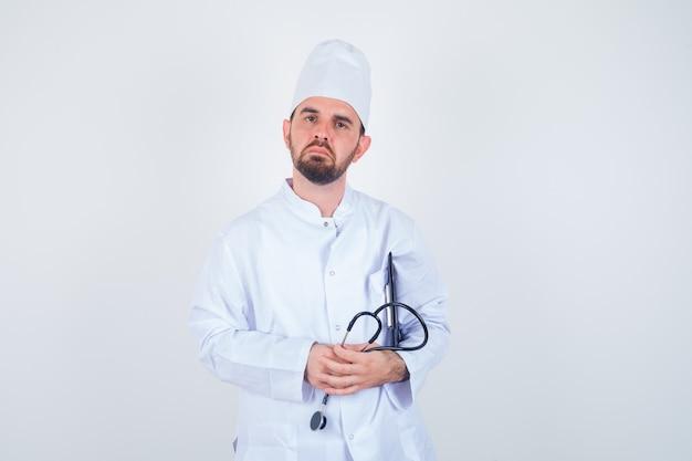 Junger männlicher arzt, der klemmbrett und stethoskop in der weißen uniform hält und vorsichtig schaut, vorderansicht.
