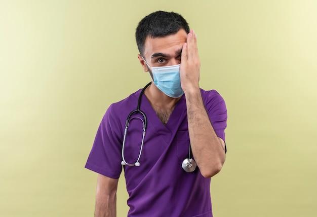 Junger männlicher arzt, der lila chirurgenkleidung und medizinische maske des stethoskops trägt, bedeckte auge mit hand auf isolierter grüner wand