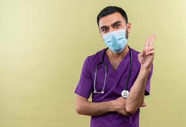 Junger männlicher arzt, der lila chirurgenkleidung und medizinische stethoskopmaske trägt, die friedensgeste auf isolierter grüner wand zeigt