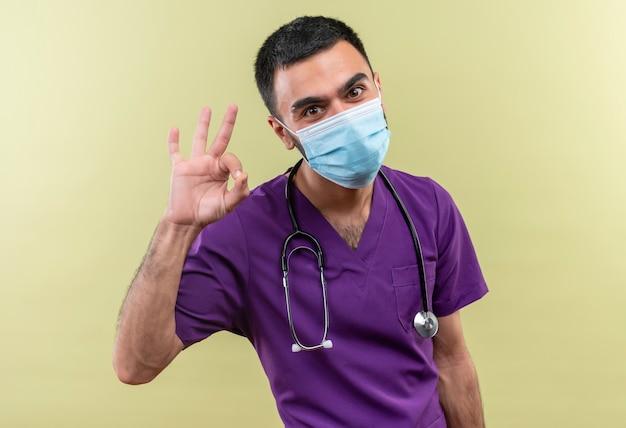 Junger männlicher arzt, der lila chirurgenkleidung und medizinische stethoskopmaske trägt, die okey geste auf isolierter grüner wand zeigt