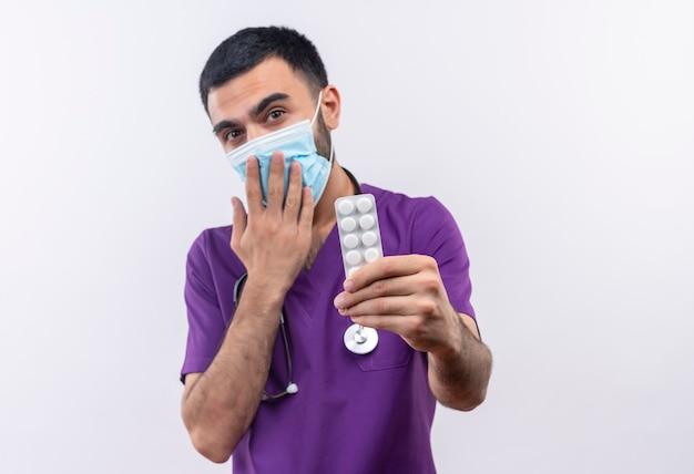 Junger männlicher arzt, der lila chirurgenkleidung und medizinische stethoskopmaske trägt, die pillen zum kamerabedeckten mund mit hand auf isolierter weißer wand heraushalten