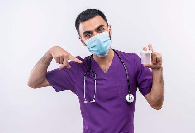 Junger männlicher arzt, der lila chirurgenkleidung und medizinische stethoskopmaske trägt, zeigt auf leere dose in seiner hand auf isolierter weißer wand