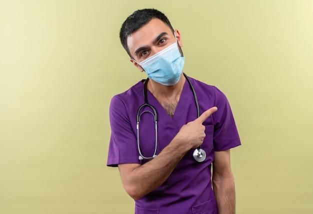 Junger männlicher arzt, der lila chirurgenkleidung und medizinische stethoskopmaske trägt, zeigt seitlich mit dem finger auf isolierte grüne wand