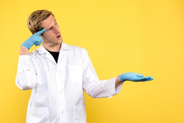 Junger männlicher arzt der vorderansicht auf einer gelben schreibtisch-pandemie des menschlichen covid medic