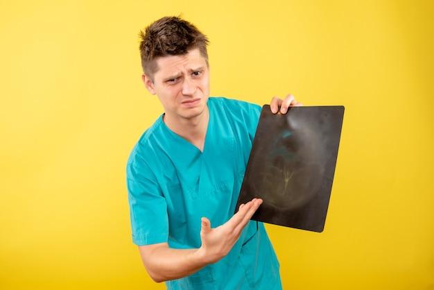 Junger männlicher arzt der vorderansicht im medizinischen anzug, der röntgenstrahl auf gelbem hintergrund hält