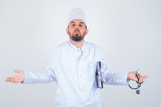 Junger männlicher arzt hält zwischenablage und stethoskop, zeigt hilflose geste in der weißen uniform und schaut verwirrt, vorderansicht.