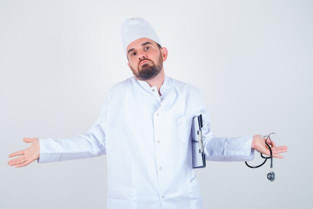 Junger männlicher arzt hält zwischenablage und stethoskop, zeigt hilflose geste, indem er in weißer uniform zuckt und verwirrt aussieht. vorderansicht.