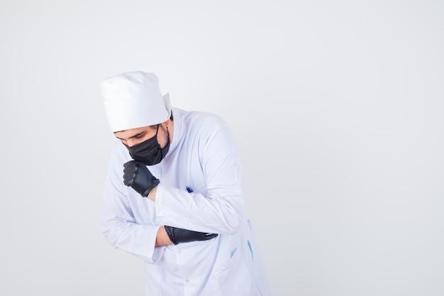 Junger männlicher arzt hustet, während er in weißer uniform steht und unwohl aussieht. vorderansicht.
