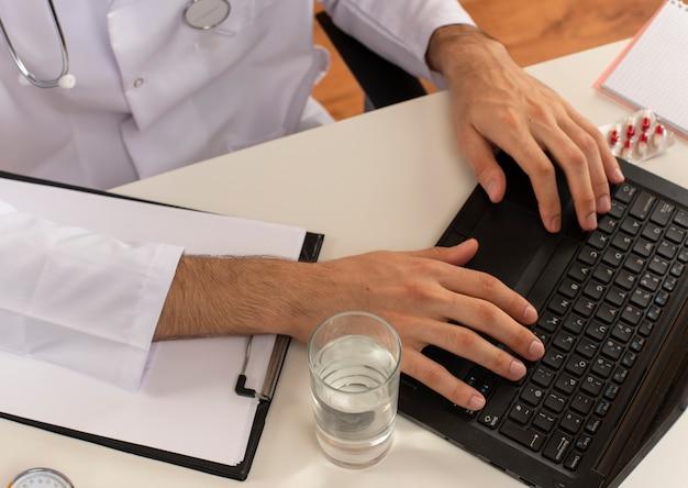 Junger männlicher arzt mit medizinischer brille, der ein medizinisches gewand mit stethoskop trägt, das am schreibtisch sitzt