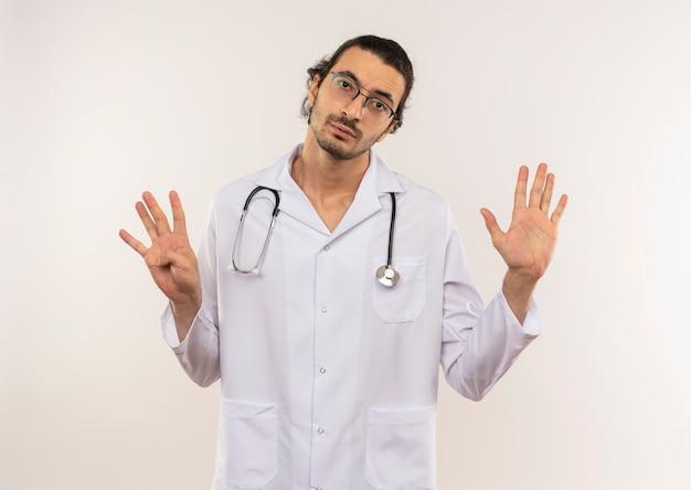 Junger männlicher arzt mit optischer brille, die weiße robe mit stethoskop trägt, das verschiedene zahlen zeigt