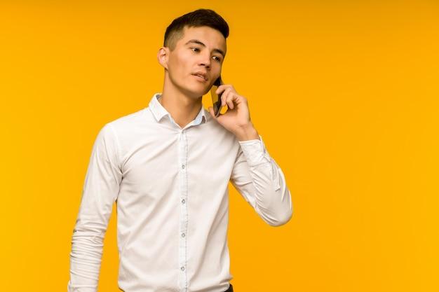 Junger männlicher asiatischer geschäftsmann, der ernsthaft am telefon spricht