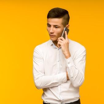 Junger männlicher asiatischer geschäftsmann, der ernsthaft am telefon spricht.