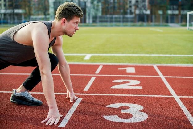 Junger männlicher athlet bereit zu laufen, stellung an der startlinie nehmend