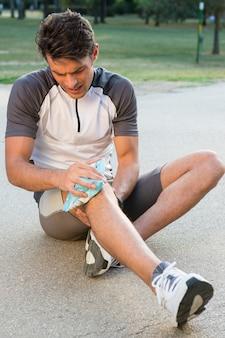 Junger männlicher athlet, der auf boden sitzt und eis für knieschmerzen nimmt